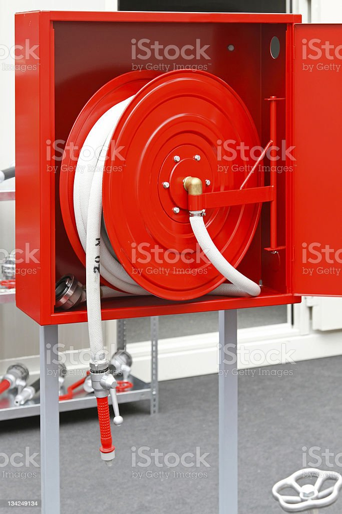 Red and white fire hose in a red box  stock photo