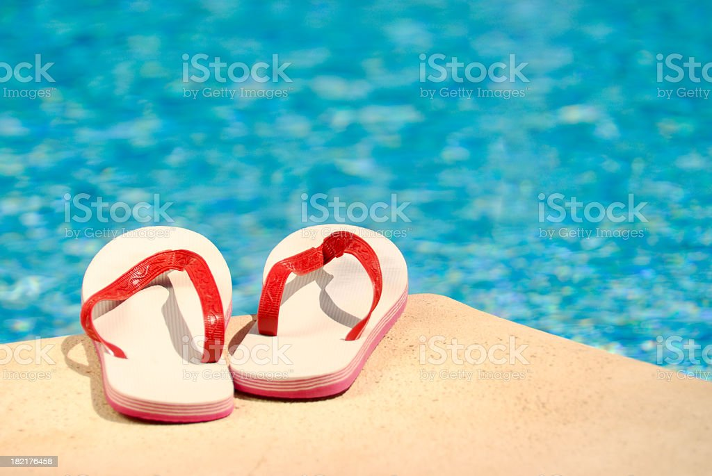 Red and white flip flops on pools edge stock photo