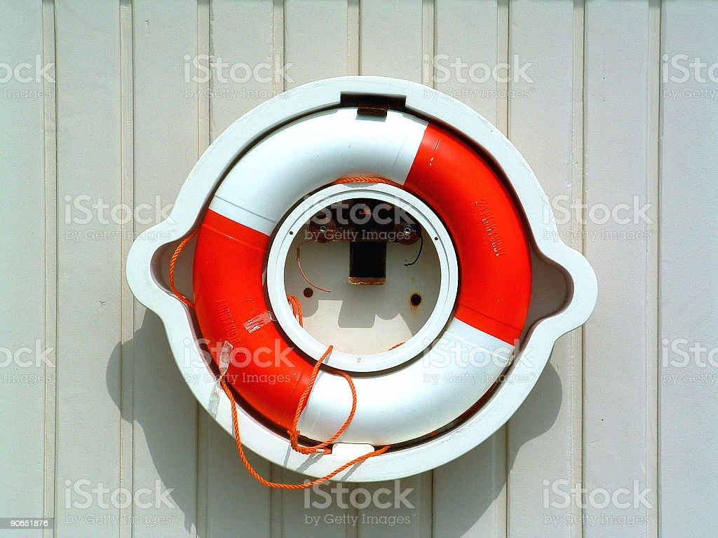 Red and white life preserver, buoy, stored on a wall stock photo