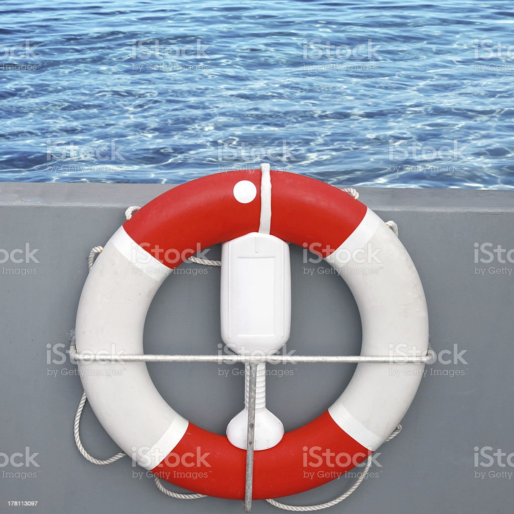 Red and white lifebuoy with rope royalty-free stock photo