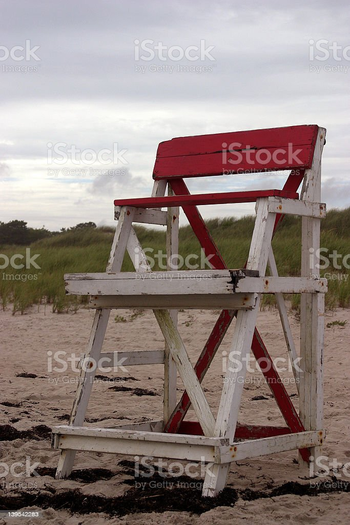 Red and White Lifeguard Chair on beach stock photo