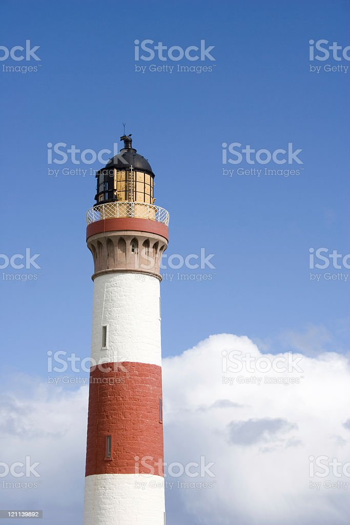 Red and white lighthouse against blue sky royalty-free stock photo