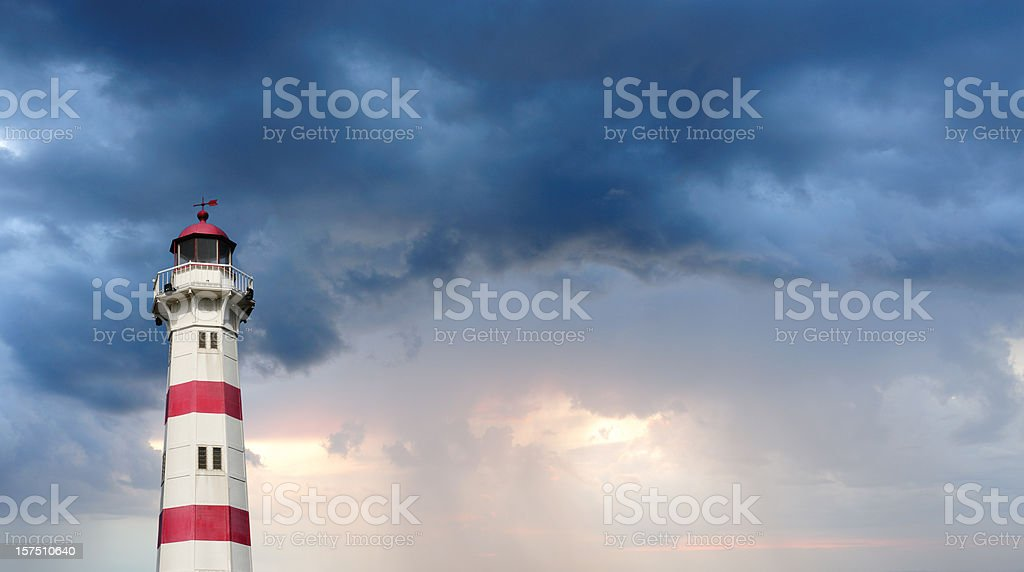 Red and white lighthouse against dramatic sky royalty-free stock photo