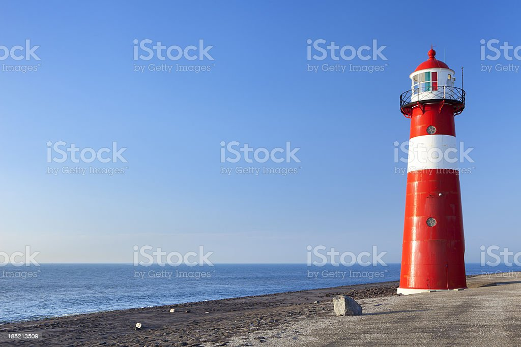 Red and white lighthouse and a clear blue sky stock photo