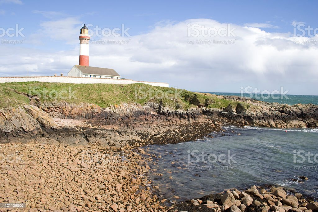 Red and white lighthouse on rocks royalty-free stock photo