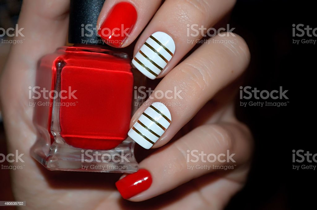 Red and white nail design with red polish bottle stock photo