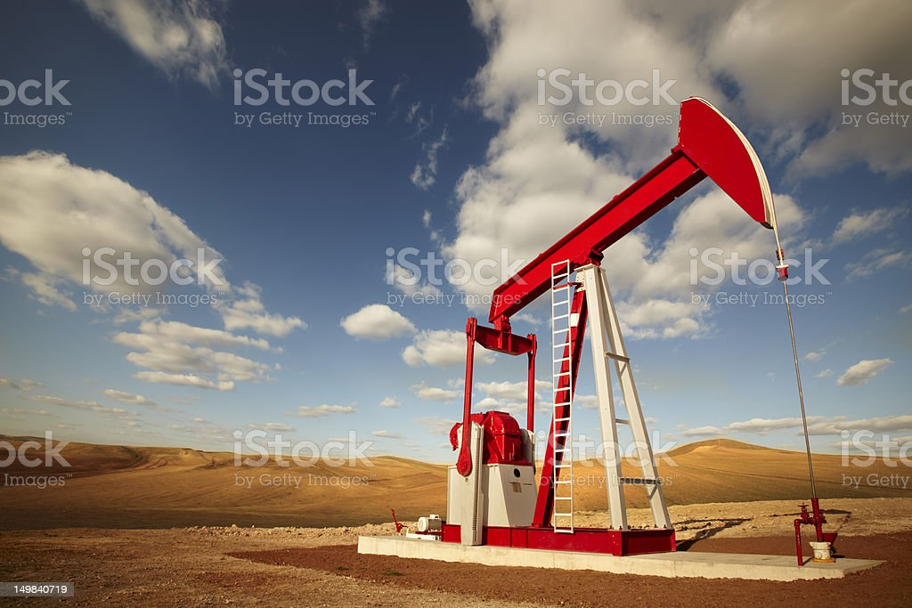A red and white oil well and a cloudy sky stock photo
