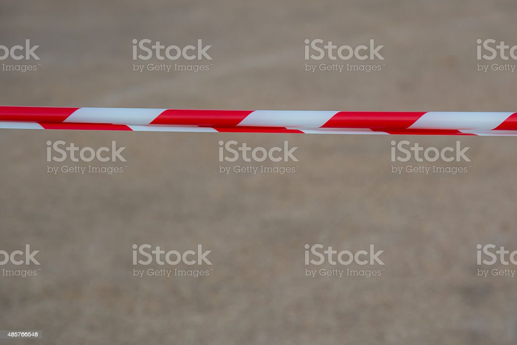 Red and white plastic barrier tape blocking the way. stock photo