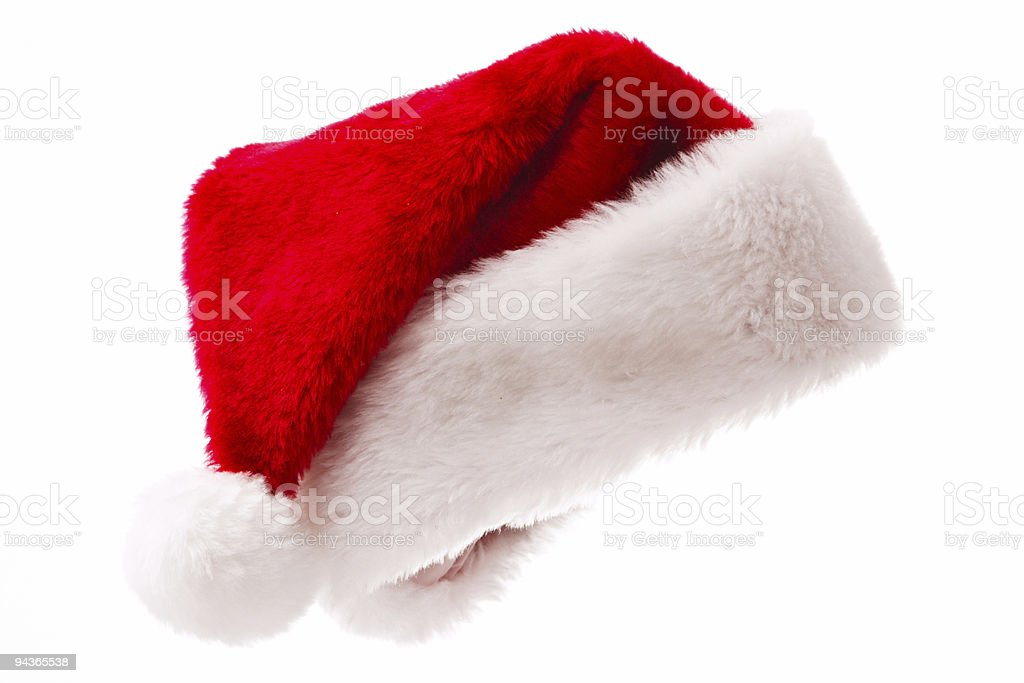 Red and white plush Santa hat over a white background stock photo
