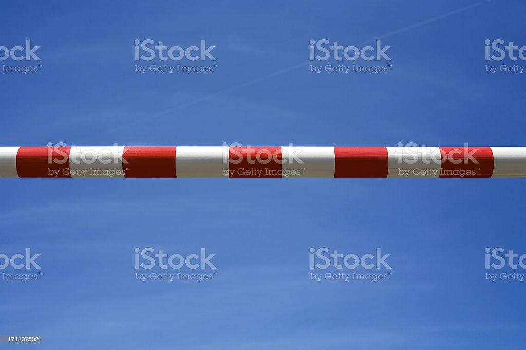 Red and white road barrier against blue sky stock photo