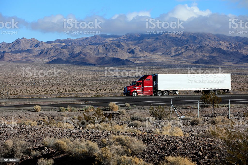 Red And White Semi Traveling California Highway To LA stock photo