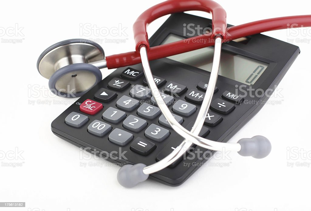 Red and white stethoscope on top of a black calculator royalty-free stock photo