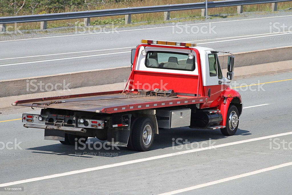 Red and white tilt bed tow truck on an empty highway royalty-free stock photo