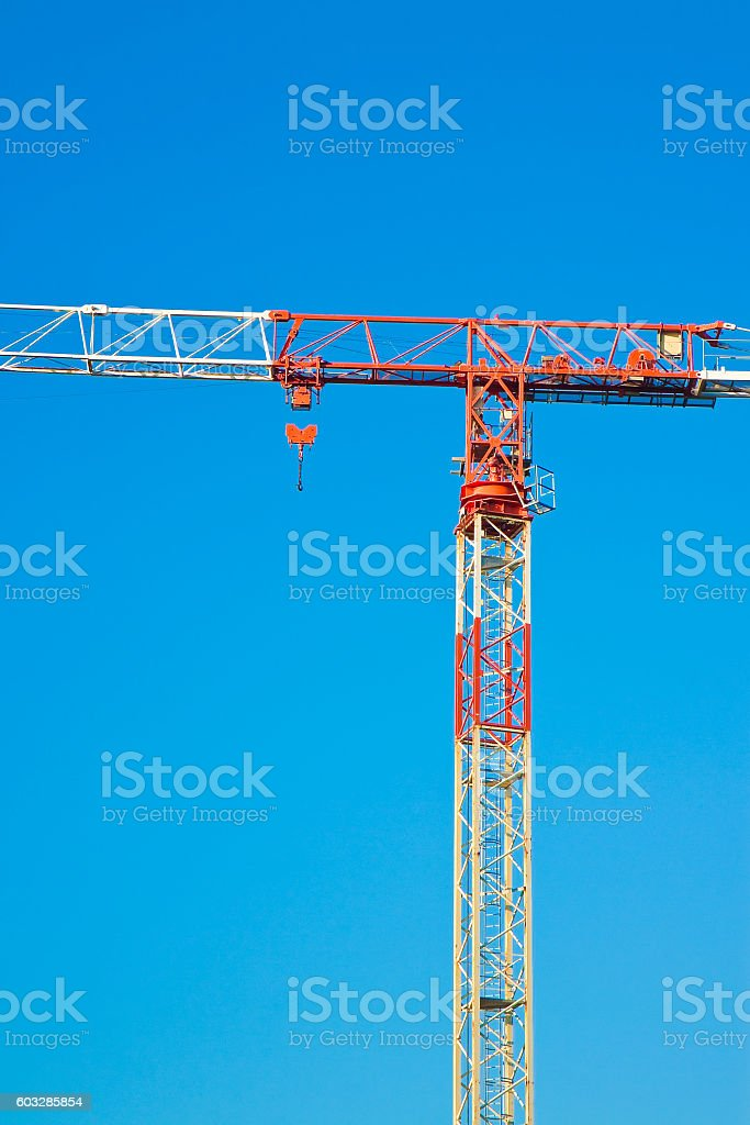 Red and white tower crane in a blue background stock photo