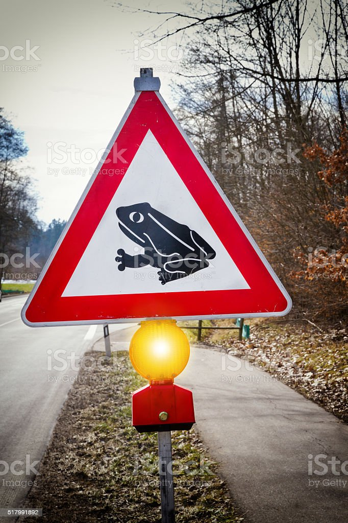 Red and white triangular road sign with a Frog stock photo