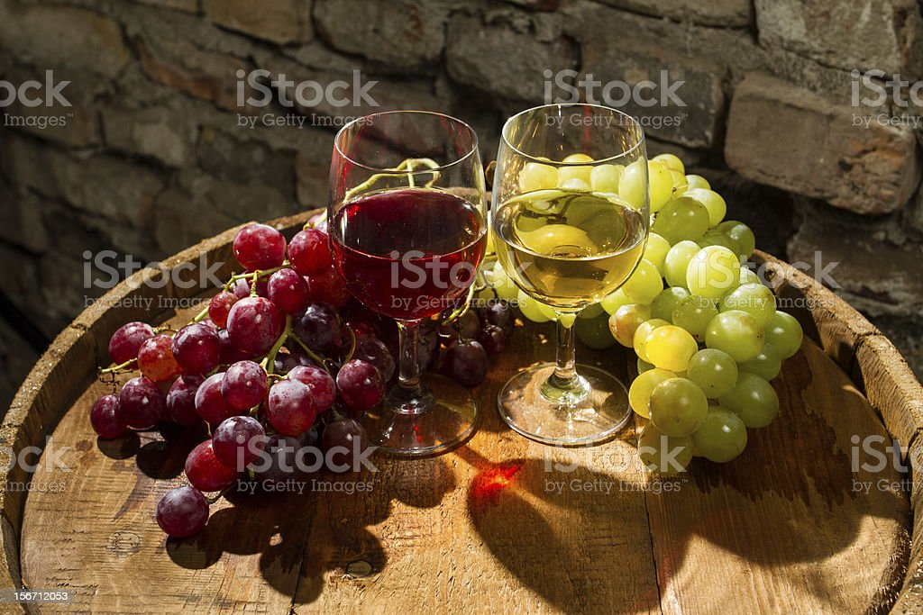 Red and white wine between bunches of grapes royalty-free stock photo