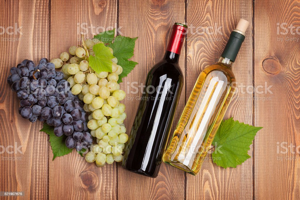 Red and white wine bottles and bunch of grapes stock photo