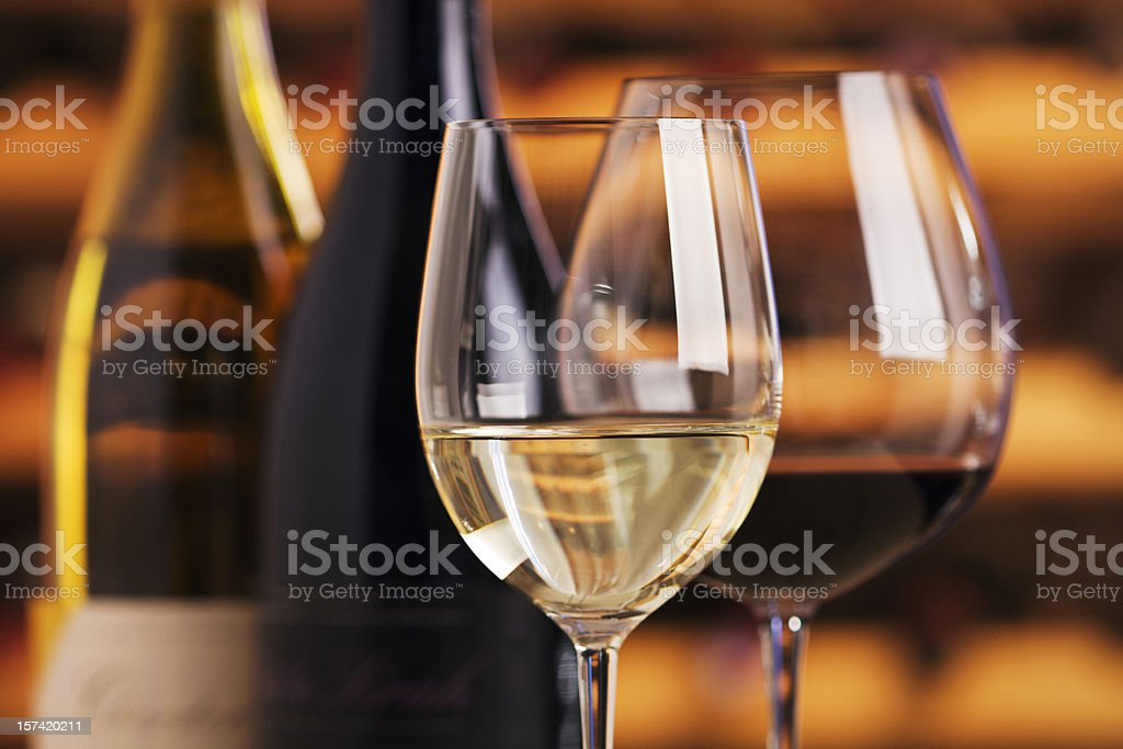 Red and White Wine in Glasses with Bottles, Cellar Background stock photo