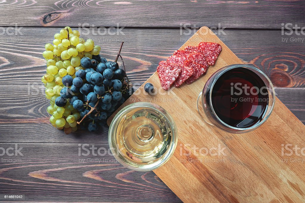 Red and white wine on a wooden table stock photo
