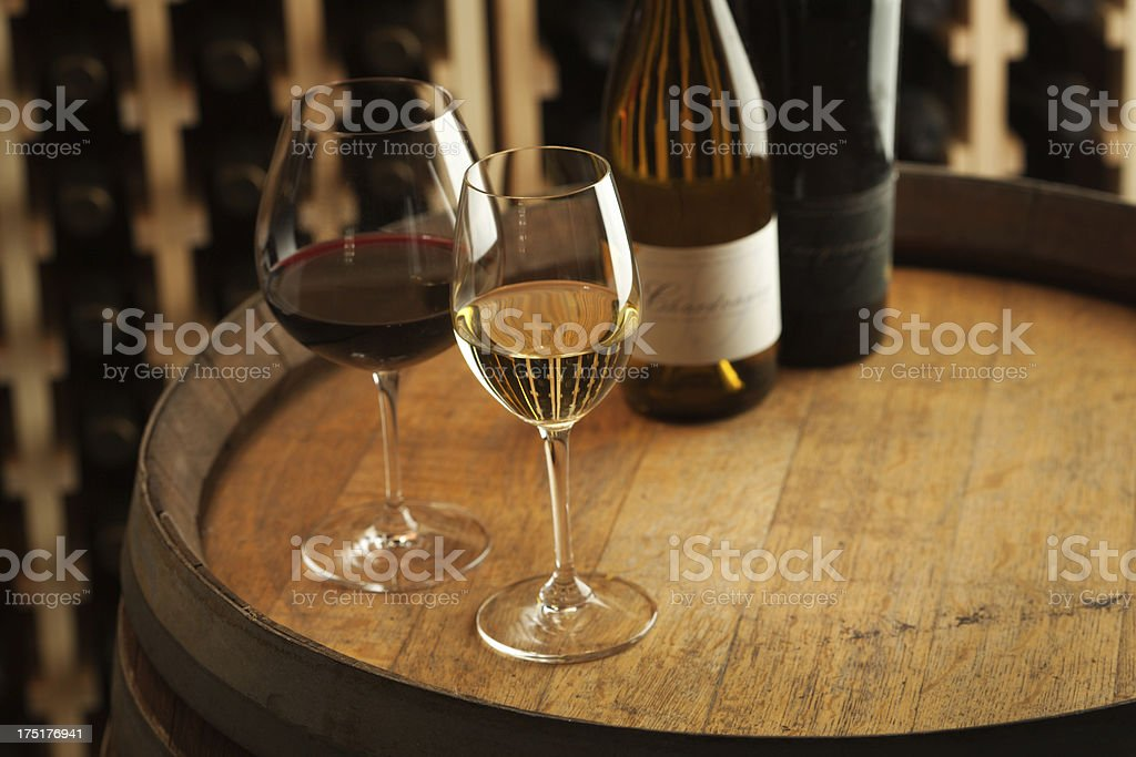 Red and White Wine Winetasting Glasses, Bottles on Cellar Barrel stock photo