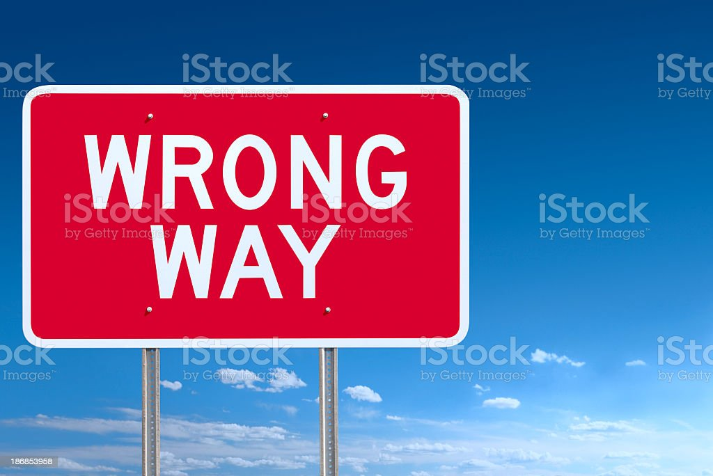 Red and White Wrong Way Road Sign Post Over Sky stock photo