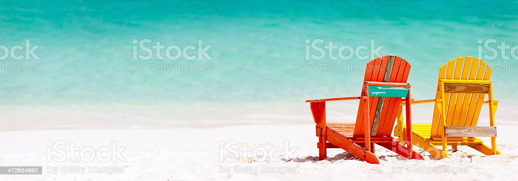 Red and yellow Adirondack chairs, on a Caribbean beach stock photo
