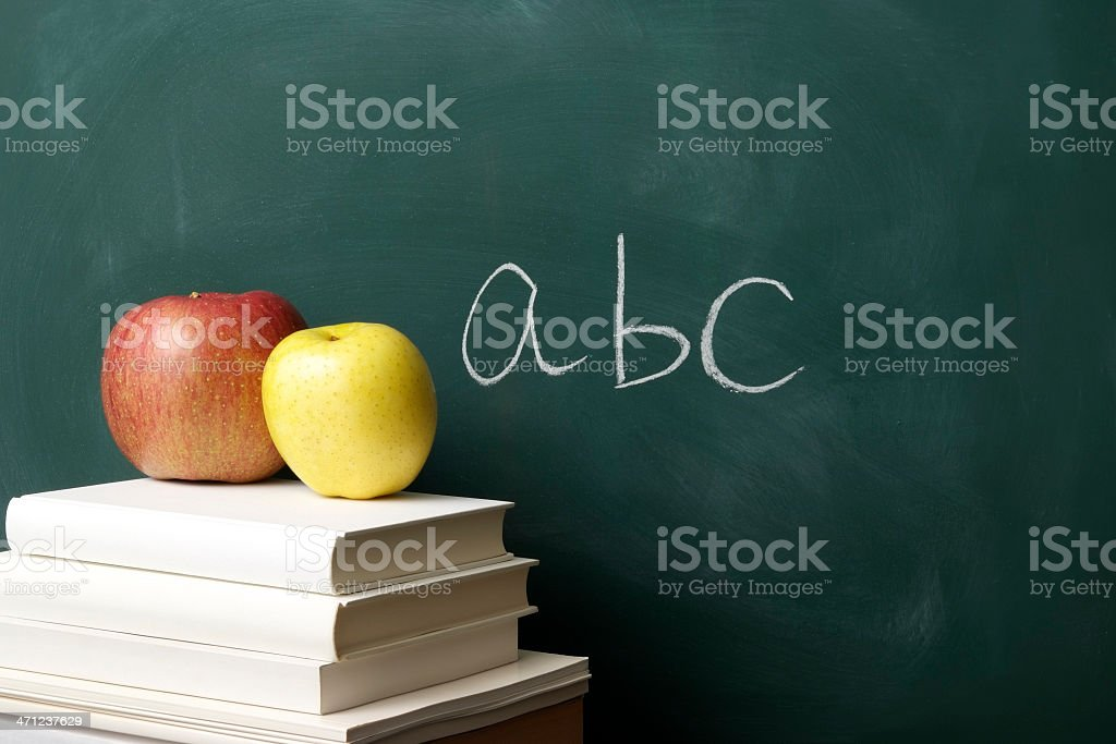 Red and yellow apple on stacked blank books against blackboard royalty-free stock photo