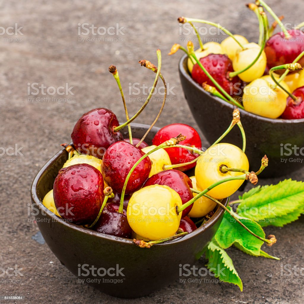 Red and yellow cherries in dark ceramic bowls on a dark background. Top view stock photo