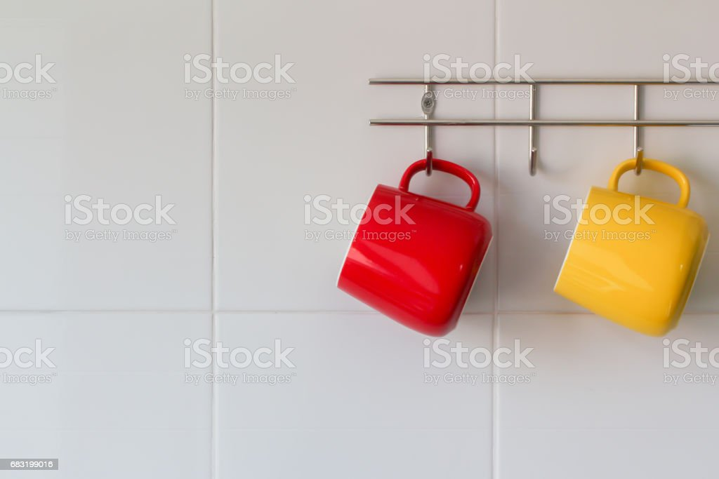 red and yellow cup on wall stock photo