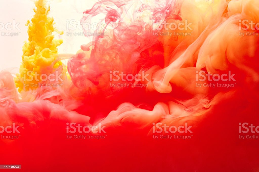 Red and yellow inks making clouds in water stock photo