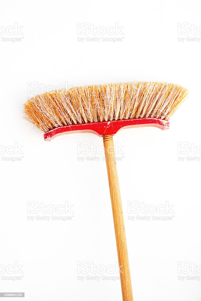 Red and Yellow Pushbroom On Whitewashed Wall stock photo