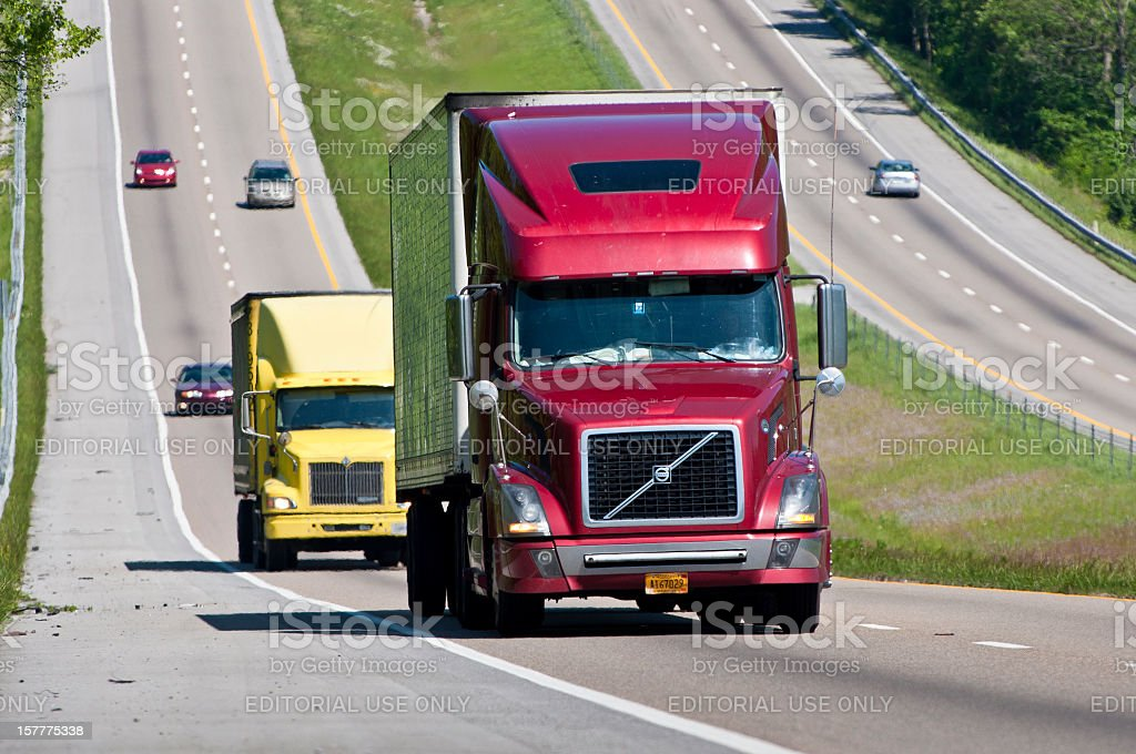 Red and Yellow Semi Trucks Climb Hill On Interstate stock photo