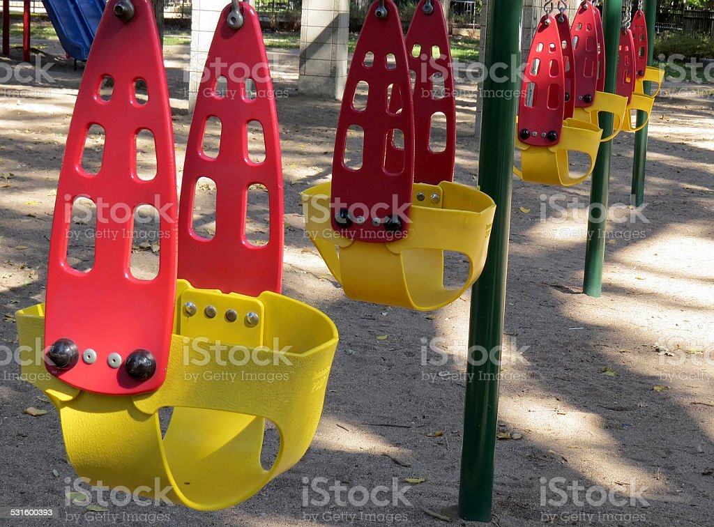 Red and yellow swings in park stock photo