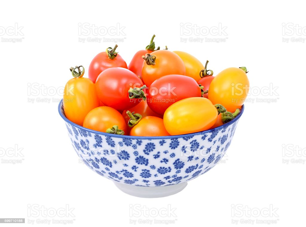 Red and yellow tomatoes in a china bowl stock photo