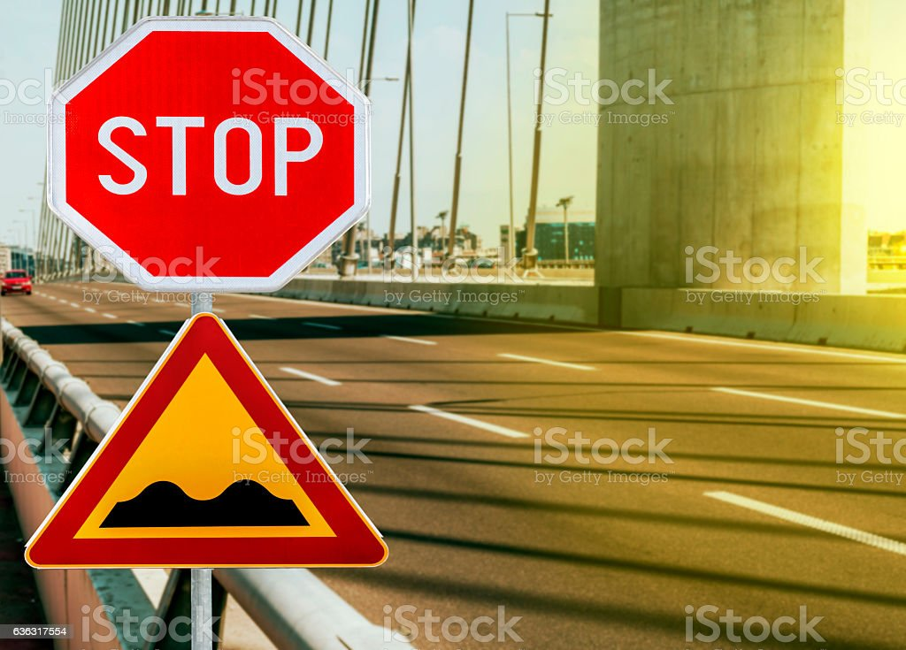 Red and yellow triangular warning road sign with STOP sign stock photo