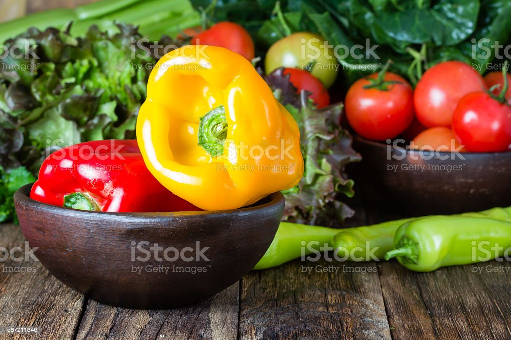Red and yelow bell pepper in clay bowl stock photo
