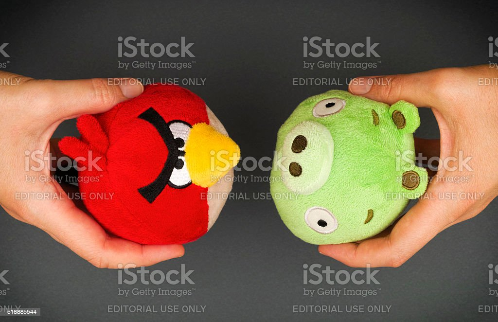 Red Angry Bird & Bad Piggy soft toys in hands stock photo