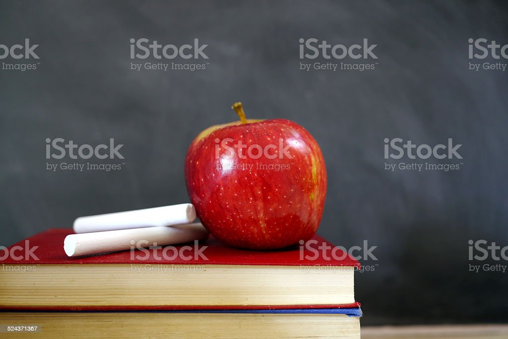 red apple and chalk on books stock photo