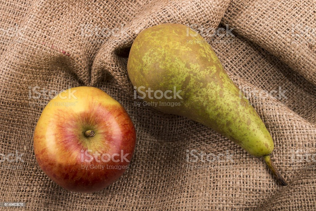red apple and green pear on jute stock photo