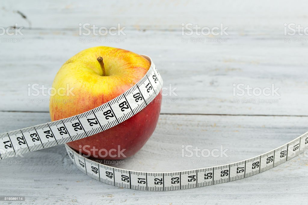 Red apple and measuring tape on wooden background stock photo