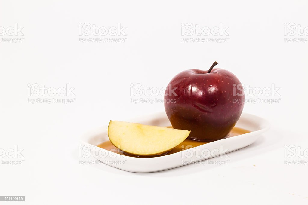 Red apple and red apple slice on plate with honey stock photo