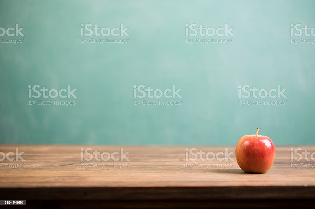 Red apple and school chalkboard on wooden desk. stock photo