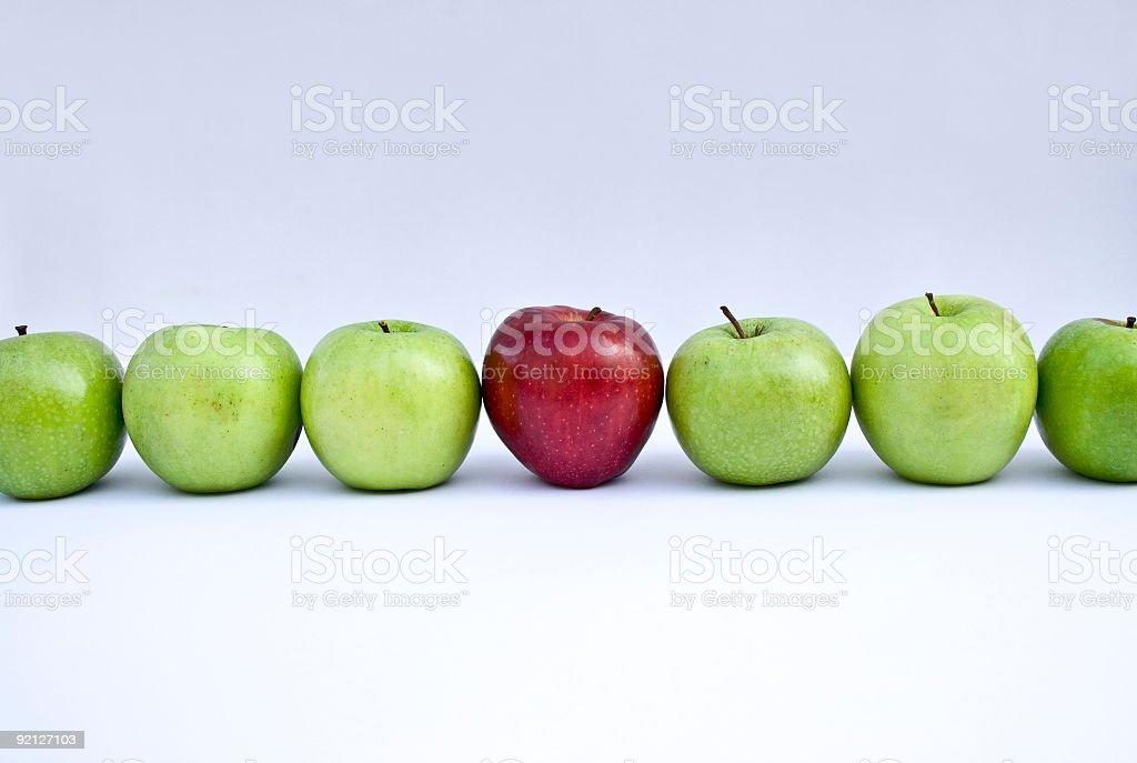 Red apple between green apples stock photo