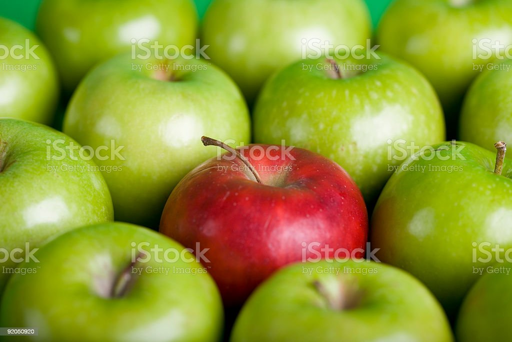 A red apple in a collection of green apples stock photo