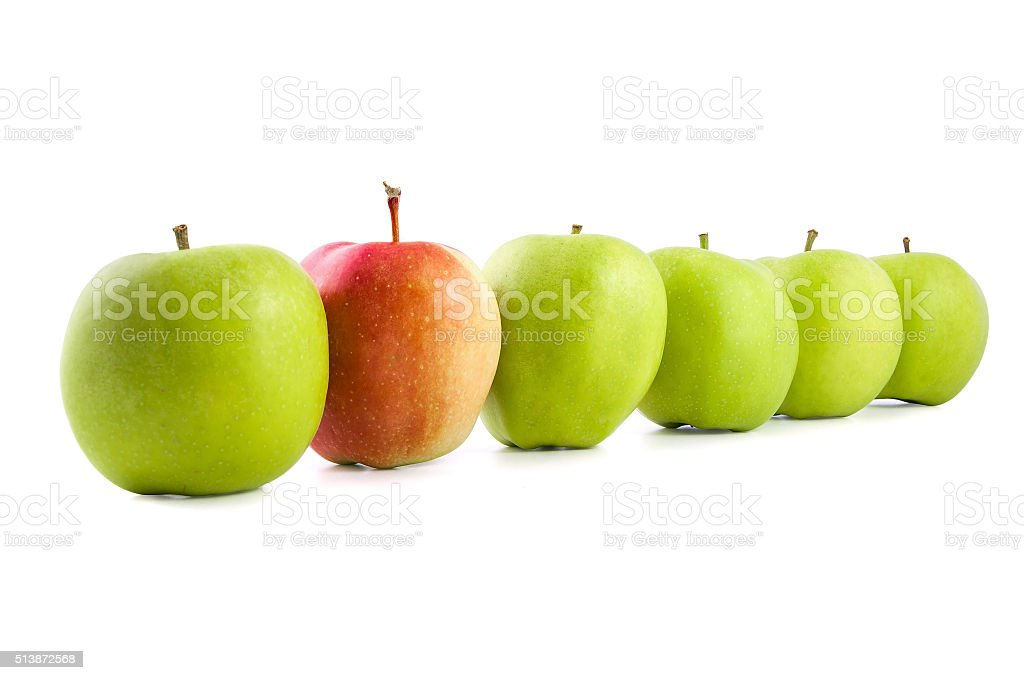 Red apple in a row of green apples stock photo