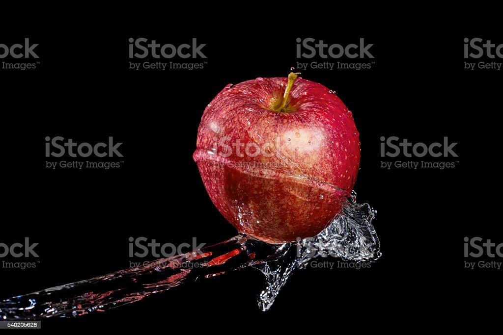 Red apple in water splash against black background stock photo