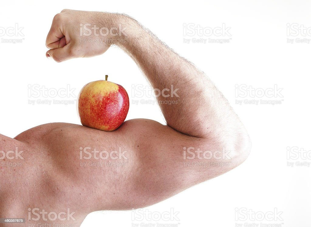 Red Apple on male Bicep Muscle stock photo