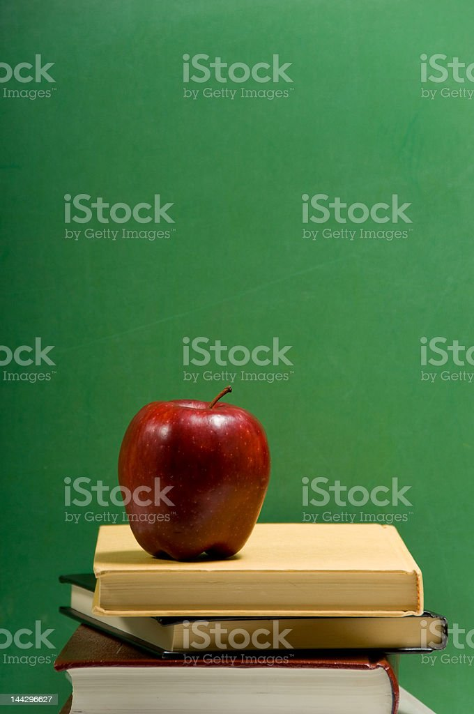 red apple on school books with green background royalty-free stock photo