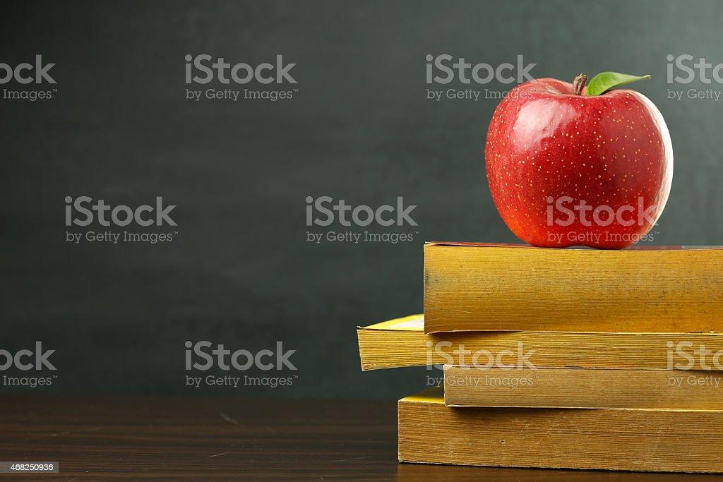 Red apple on stack of books against chalkboard background stock photo