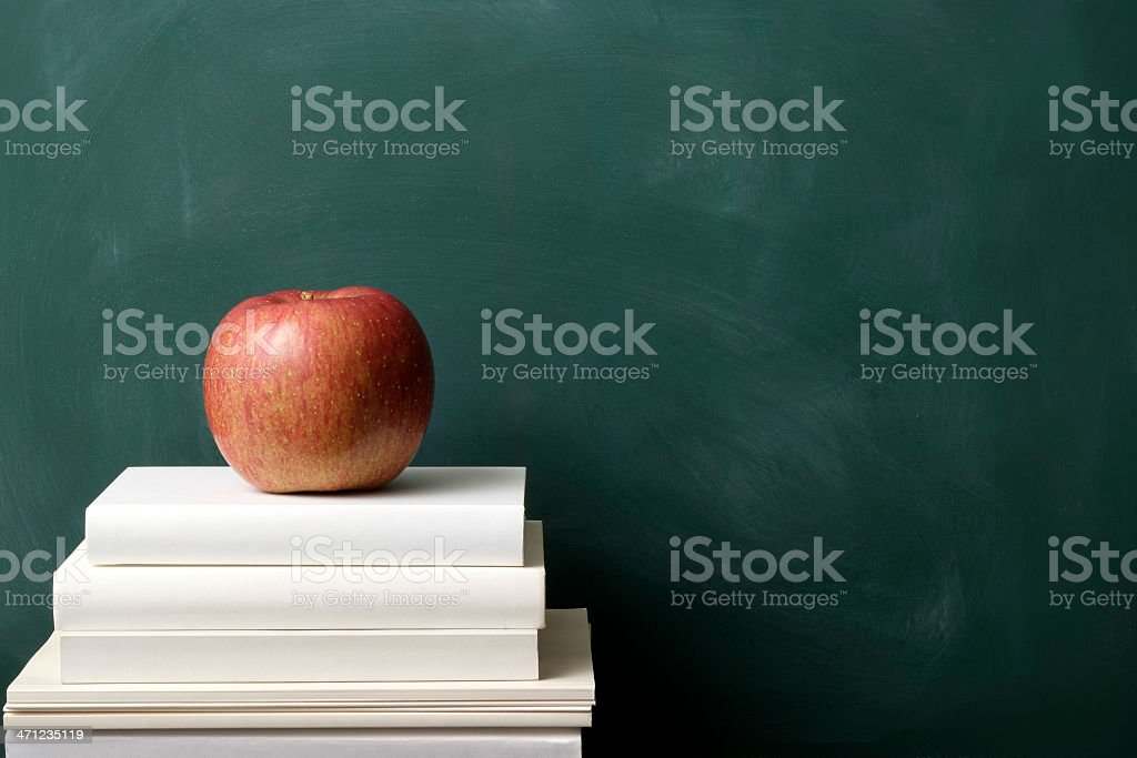 Red apple on stacked blank books against blackboard royalty-free stock photo